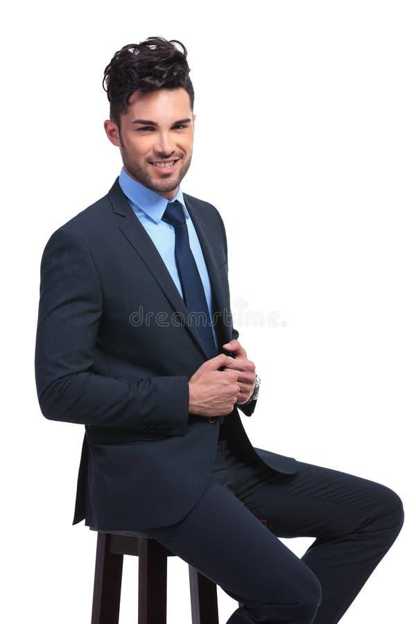 Homem de negócio novo de sorriso que senta-se em um tamborete foto de stock