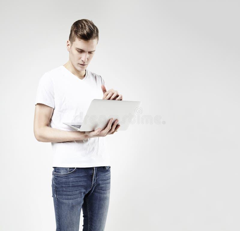 Homem de negócio novo do moderno no t-shirt branco que está com o portátil nas mãos Corpo completo, calças de brim vestindo, isol fotografia de stock royalty free