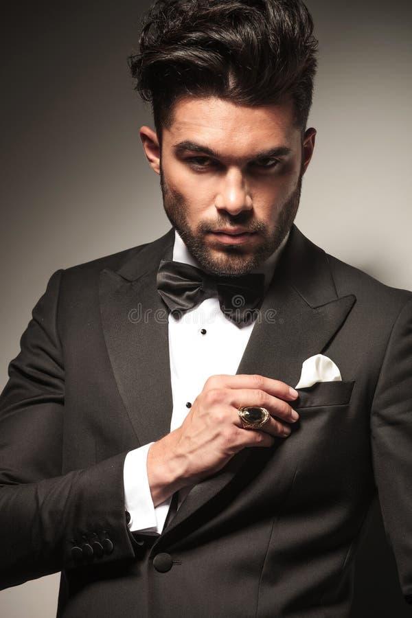Homem de negócio novo elegante que fixa seu jacke fotos de stock royalty free