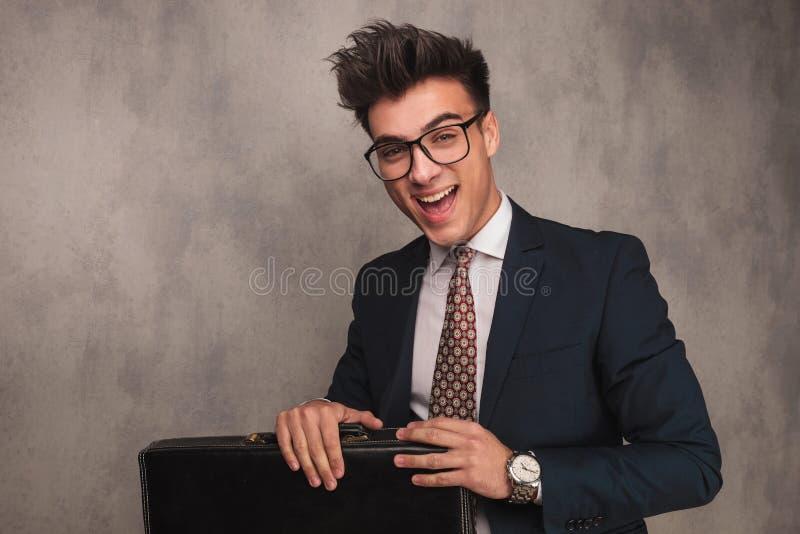 Homem de negócio novo entusiasmado que senta e que guarda a pasta fotografia de stock royalty free
