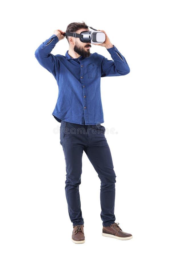 Homem de negócio novo farpado que tenta e que põe sobre os auriculares da realidade virtual que olham afastado Vista lateral imagens de stock
