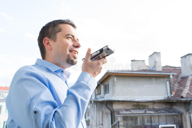 Homem de negócio novo feliz do retrato que usa o reconhecimento da mensagem da voz por seu smartphone imagens de stock royalty free