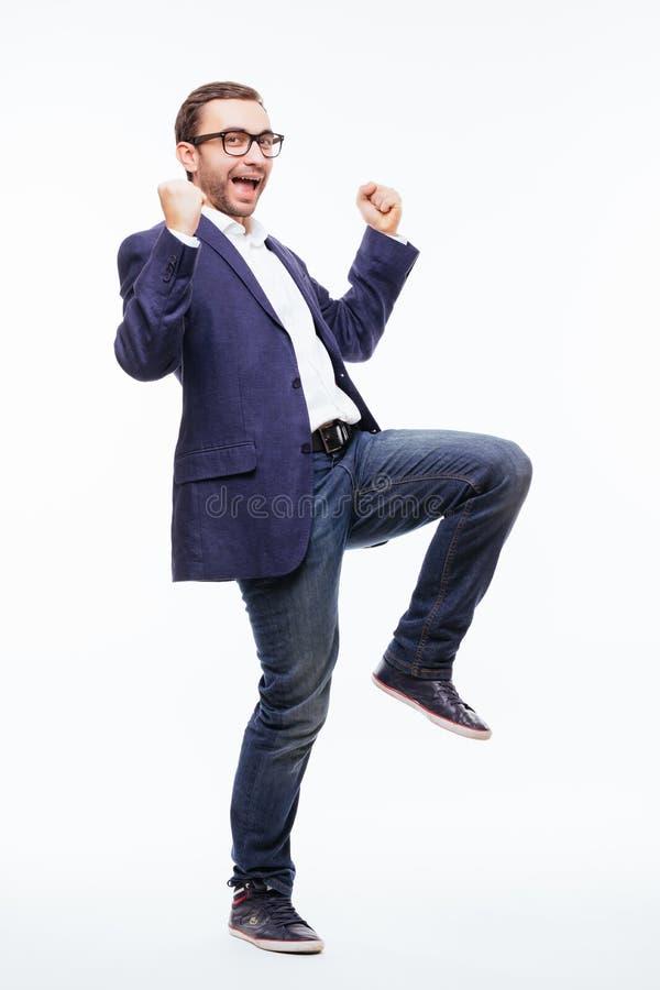 Homem de negócio novo feliz exaltado entusiasmado com a barba no salto clássico do terno e gritaria sobre o fundo branco imagens de stock royalty free