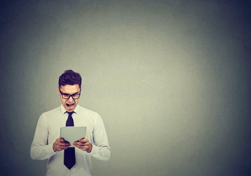 Homem de negócio novo irritado nos vidros usando uma tabuleta que grita fotografia de stock