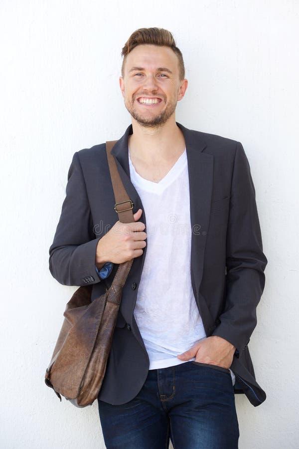 Homem de negócio novo moderno com saco que sorri contra a parede branca imagem de stock royalty free
