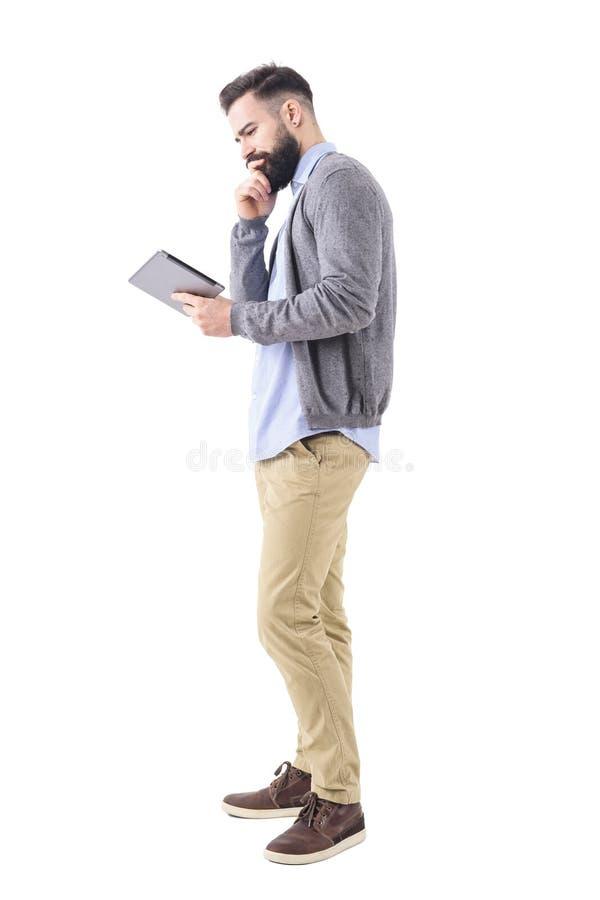 Homem de negócio novo de pensamento que olha a tabuleta com mão no queixo imagens de stock