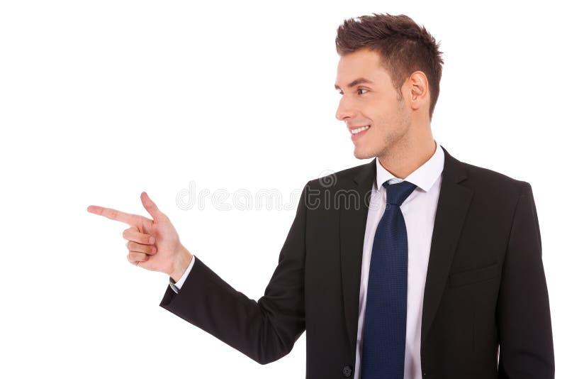 Homem de negócio novo que aponta ao lado foto de stock royalty free