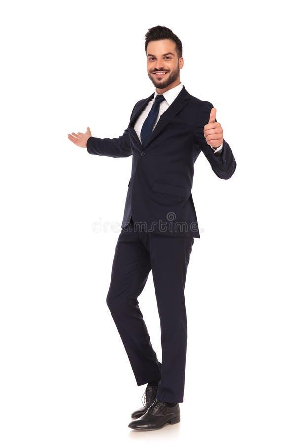 Homem de negócio novo que apresenta e que faz o sinal aprovado da mão fotos de stock