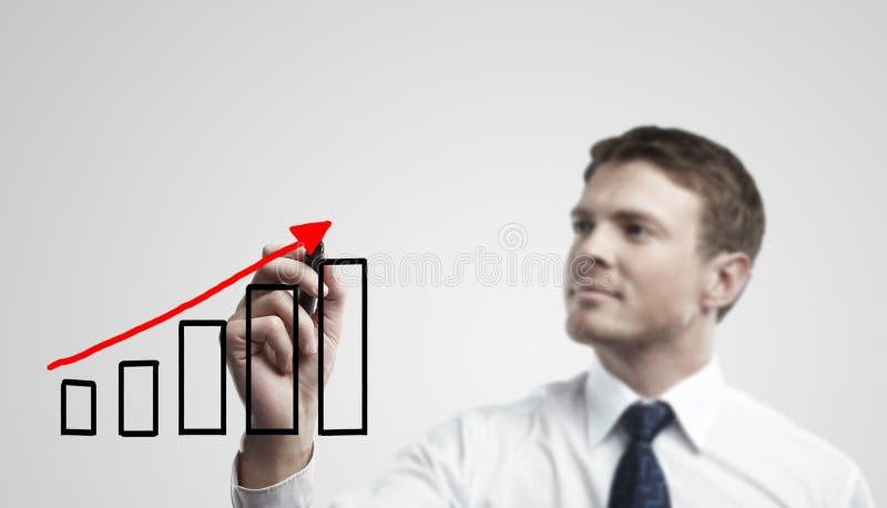 Homem de negócio novo que desenha um gráfico da ascensão imagens de stock royalty free