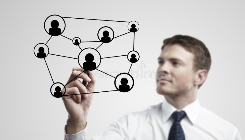 Homem de negócio novo que desenha uma rede social fotografia de stock