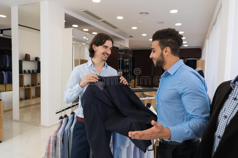 Homem de negócio novo que escolhe o terno novo durante a compra na loja imagens de stock royalty free