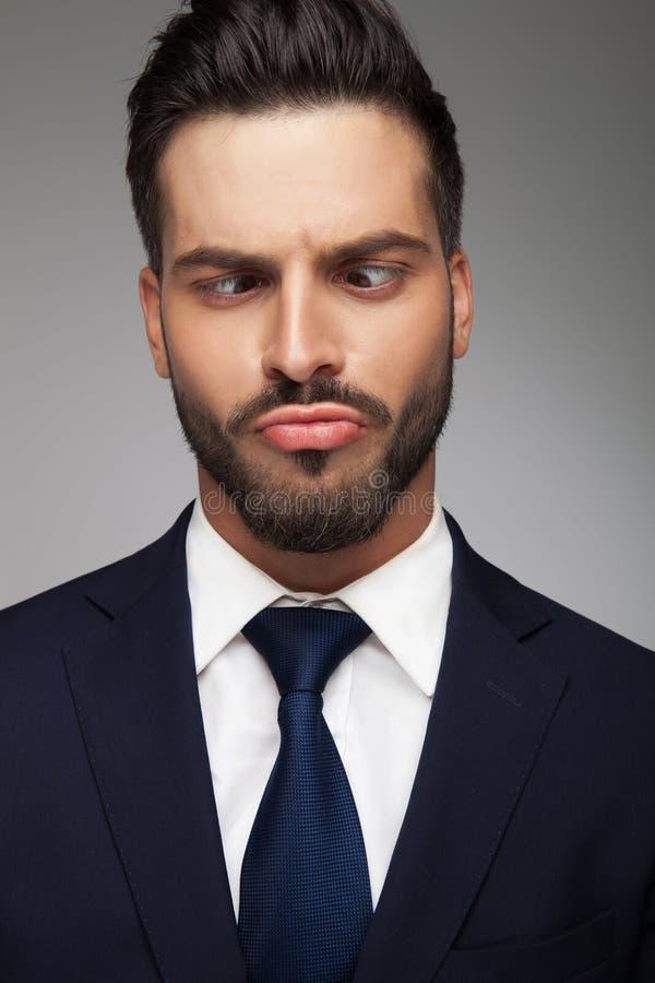 Homem de negócio novo que faz uma cara estúpida foto de stock royalty free