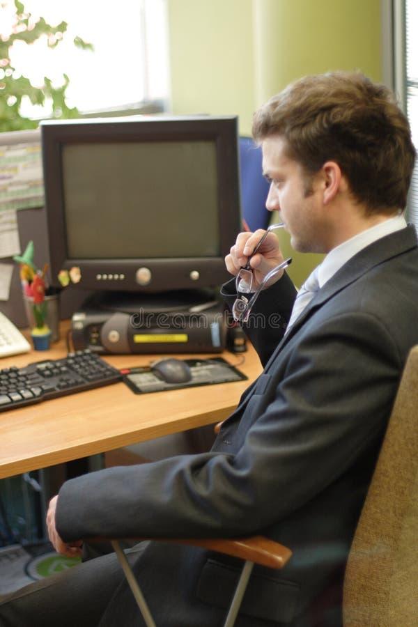Homem de negócio novo que pensa no PC imagens de stock royalty free