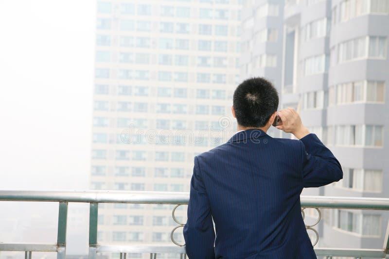 Homem de negócio novo que prende o telefone móvel fotografia de stock