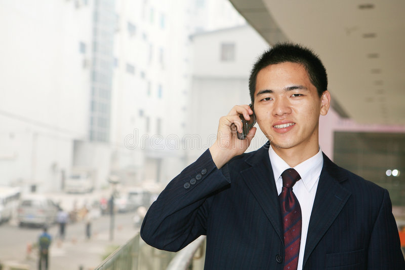 Homem de negócio novo que prende o telefone móvel imagens de stock