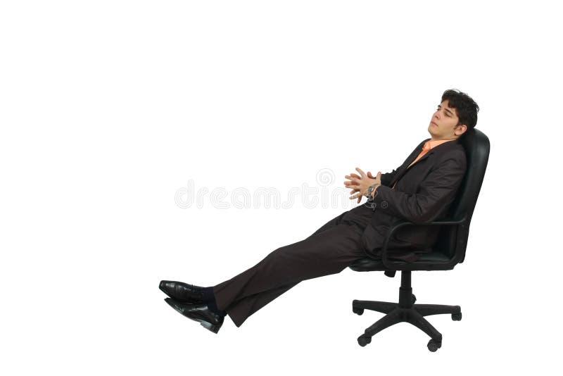 Homem de negócio novo que relaxa em uma cadeira imagens de stock royalty free