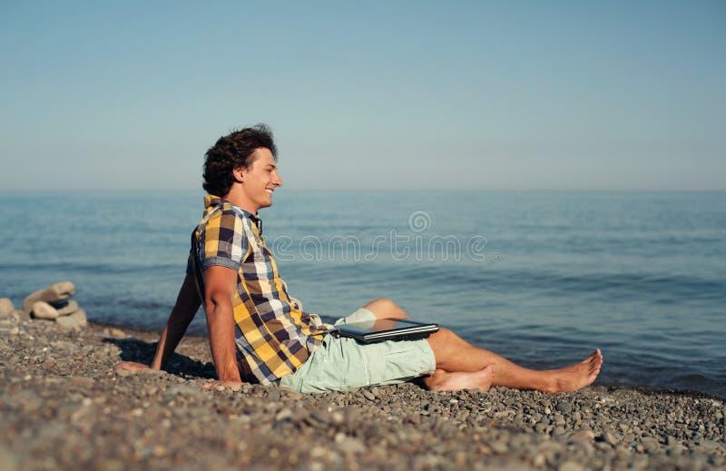 Homem de negócio novo que relaxa na praia fotografia de stock