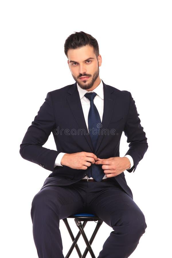 Homem de negócio novo que senta-se na cadeira e que abotoa seu revestimento fotografia de stock
