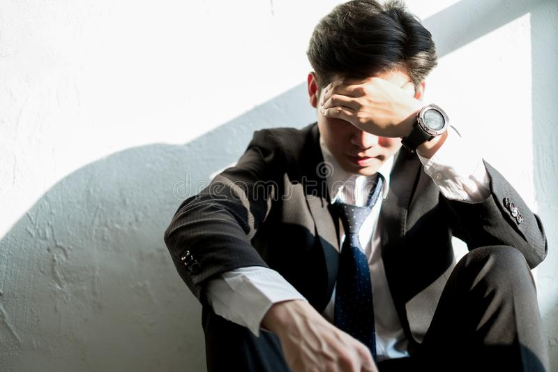 Homem de negócio novo que senta-se no escritório que sente cansado e forçado, conceito do negócio imagens de stock