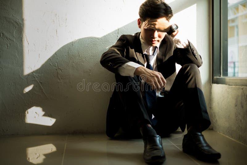 Homem de negócio novo que senta-se no escritório que sente cansado e forçado, conceito do negócio imagem de stock