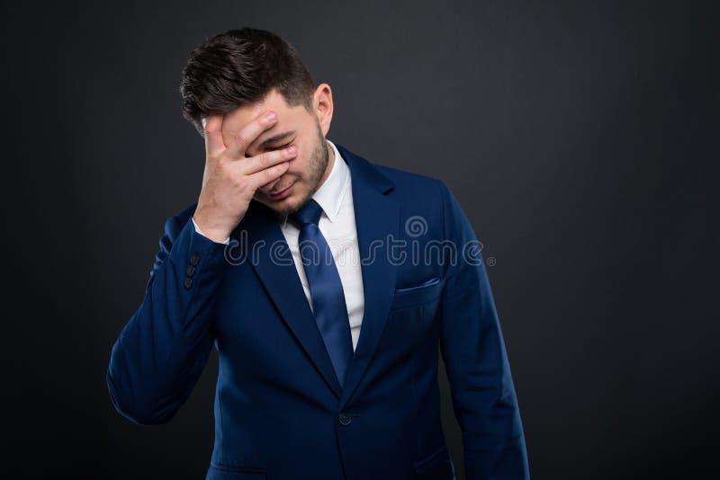 Homem de negócio novo que tem a dor de cabeça após o trabalho imagens de stock royalty free