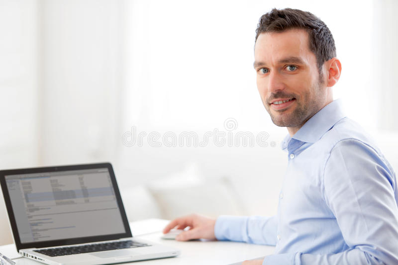 Homem de negócio novo que trabalha em casa em seu portátil fotos de stock royalty free