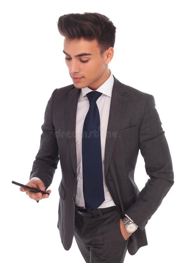 Homem de negócio novo que usa seu smartphone imagem de stock