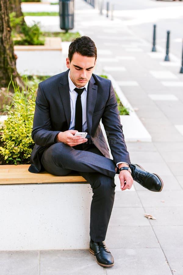 Homem de negócio novo que usa Smartphone fotografia de stock