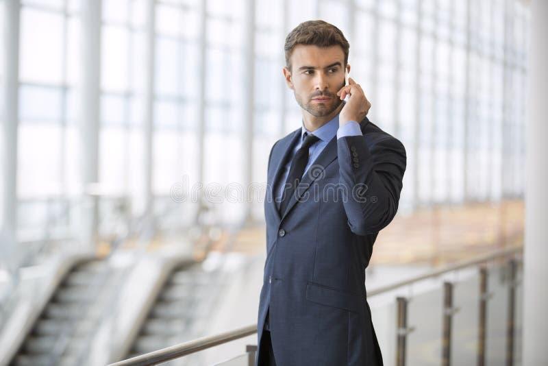 Homem de negócio novo sério no telefone imagem de stock royalty free
