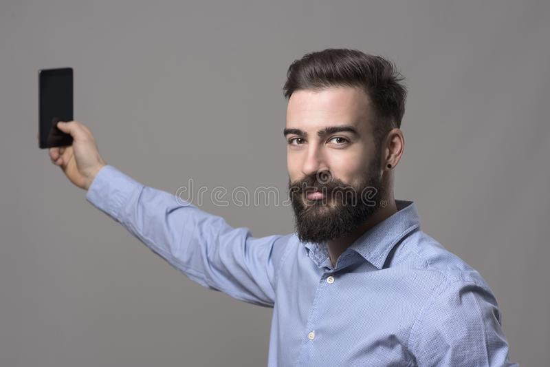 Homem de negócio novo de sorriso feliz que guarda o telefone celular que toma o selfie que olha a câmera fotografia de stock