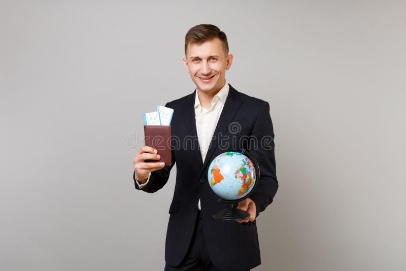 Homem de negócio novo de sorriso no passaporte preto clássico da terra arrendada do terno, bilhete da passagem de embarque, globo foto de stock