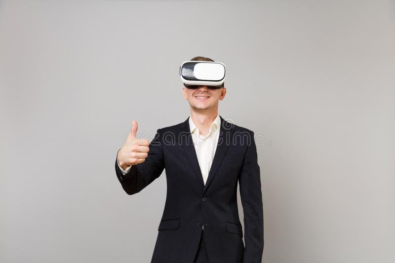 Homem de negócio novo de sorriso no terno preto clássico, camisa que olha nos auriculares, mostrando o polegar acima do isolado n imagens de stock
