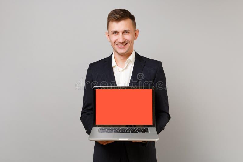 Homem de negócio novo de sorriso no terno preto clássico, computador do PC do portátil da terra arrendada da camisa com a tela va fotos de stock