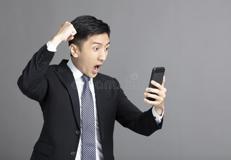 Homem de negócio novo surpreendido que olha o telefone celular fotografia de stock