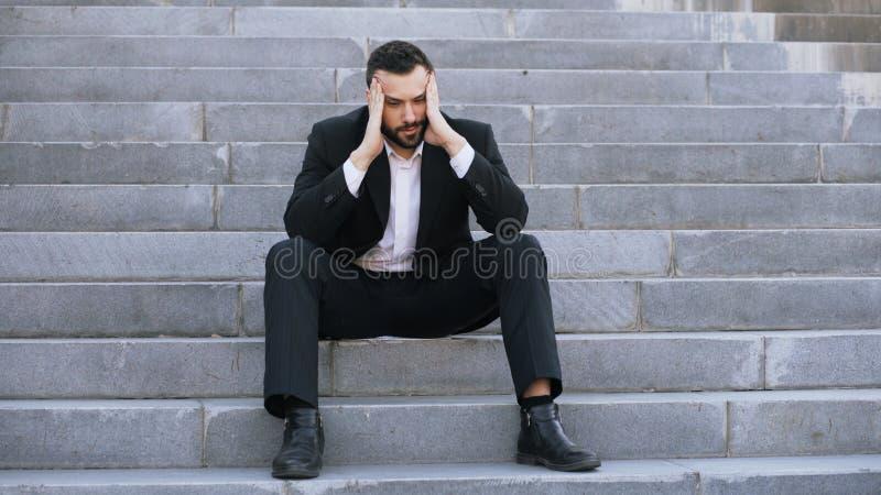 Homem de negócio novo virado que tem o esforço e que senta-se em escadas na rua Homem de negócios que tem o conceito dos problema imagens de stock royalty free