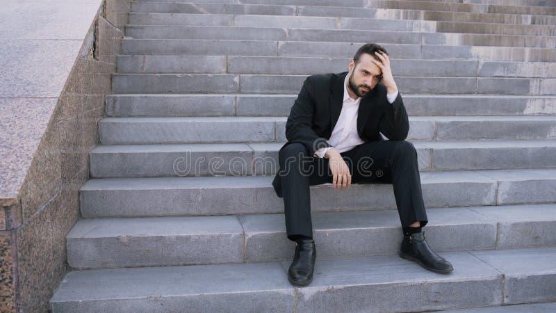 Homem de negócio novo virado que tem o esforço e que senta-se em escadas na rua Homem de negócios que tem o conceito dos problema fotos de stock royalty free