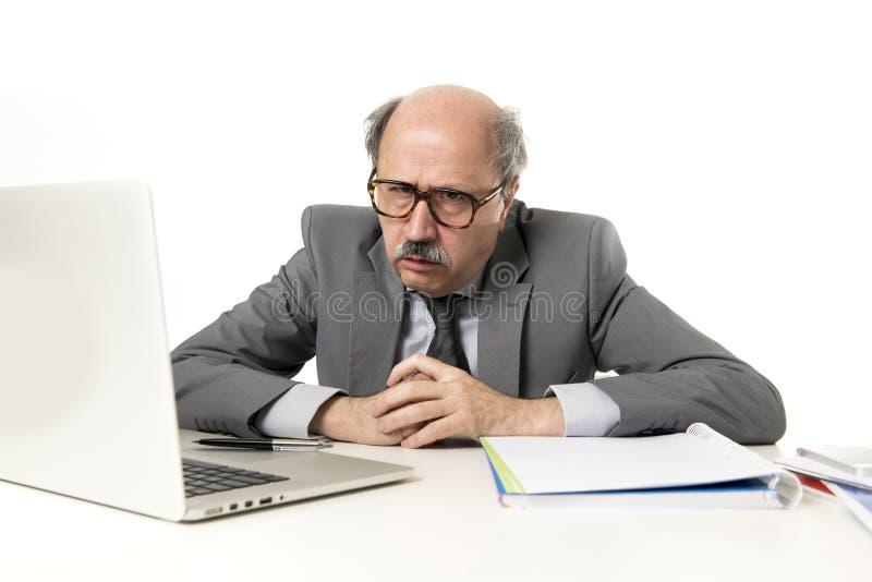Homem de negócio ocupado maduro superior com cabeça calva em seu funcionamento 60s forçado e frustrado na mesa do portátil do com fotografia de stock