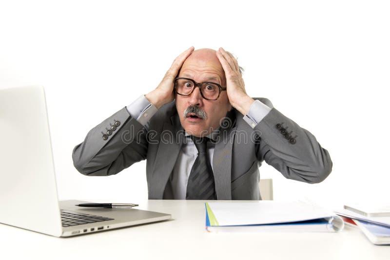 Homem de negócio ocupado maduro superior com cabeça calva em seu funcionamento 60s forçado e frustrado na mesa do portátil do com fotos de stock royalty free