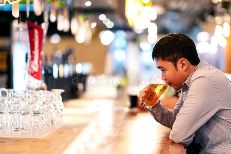 Homem de negócio ou freelancer asiático novo que sentam-se no sentimento bebendo da cerveja da barra do clube noturno pensativo Á imagens de stock royalty free