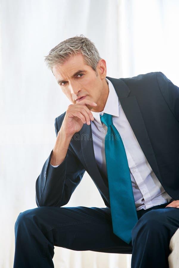 Homem de negócio pensativo na sala de hotel fotografia de stock