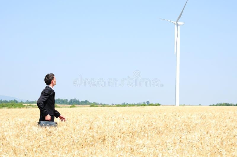 Homem de negócio perto da exploração agrícola de vento foto de stock royalty free
