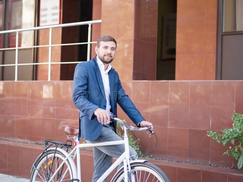 Homem de negócio positivo com uma bicicleta em um fundo da cidade conceito do transporte do eco Copie o espaço imagem de stock