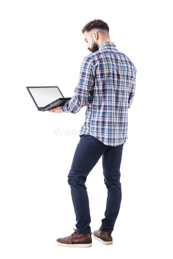Homem de negócio profissional ereto que guarda e que usa o laptop com tela vazia fotos de stock