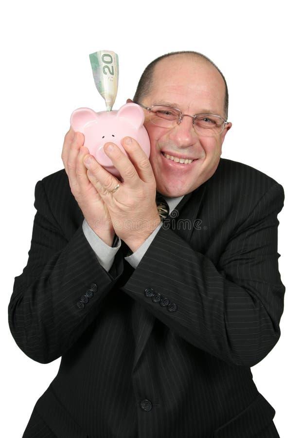 Homem de negócio que abraça o banco Piggy fotos de stock