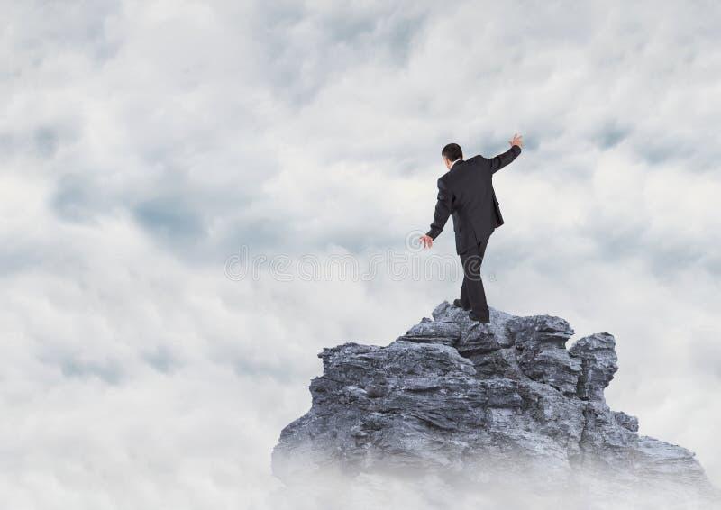 Homem de negócio que anda acima do pico de montanha nas nuvens foto de stock