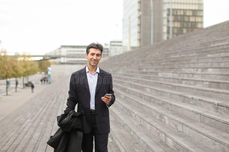 homem de negócio que anda usando o smartphone para olhar fotos fotografia de stock royalty free