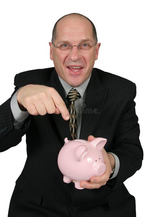 Homem de negócio que aponta ao banco Piggy fotos de stock royalty free