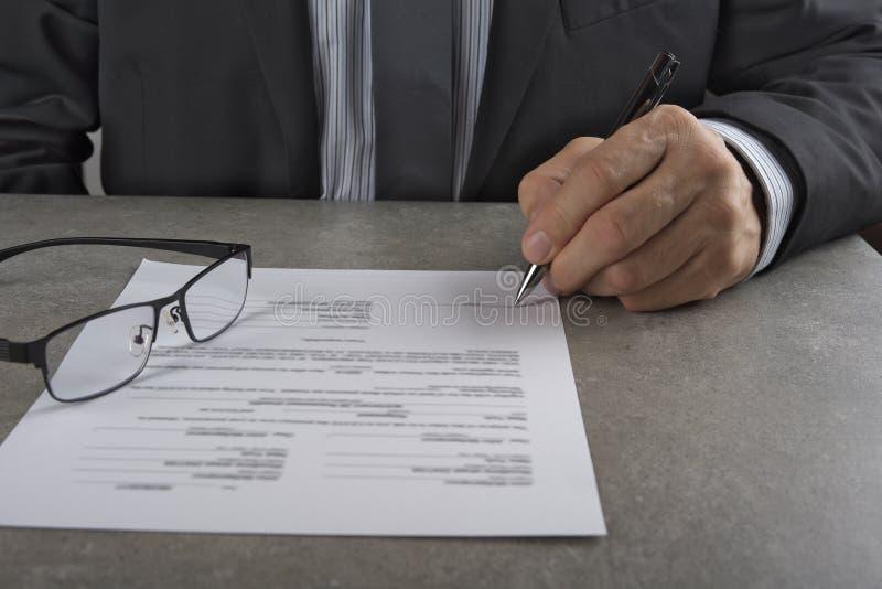 Homem de negócio que assina um contrato que faz um acordo, conceito clássico do negócio imagens de stock royalty free