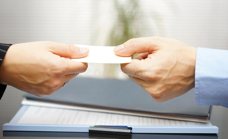Homem de negócio que cede um cartão a uma mulher fotos de stock royalty free