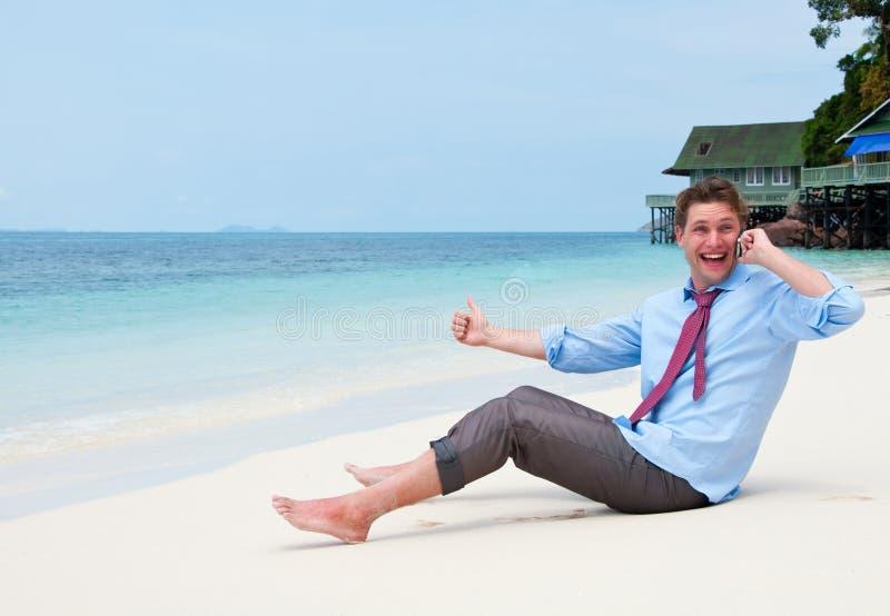 Homem de negócio que chama pelo telefone de pilha na praia imagem de stock